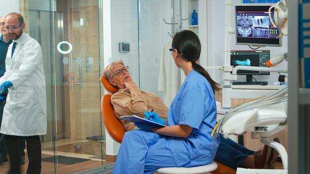 看護師に歯の問題を説明し、歯痛を示す歯痛のある患者。クリップボードにメモを取り、口腔内科検査の準備をするアシスタント。現代のcliの矯正歯科医院