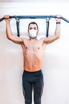 A patient without a shirt performing a dominated in the air. physiotherapy with protective measures for the coronavirus pandemic, covid-19. osteopathy, therapeutic chiromassage