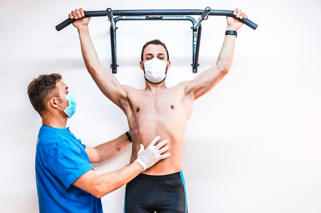 A patient without a shirt working with a physical therapist doing a pull-up. physiotherapy with protective measures for the coronavirus pandemic, covid-19. osteopathy, therapeutic chiromassage