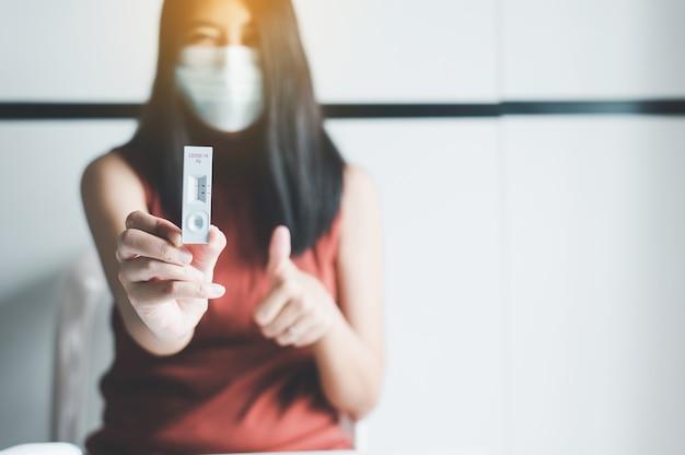 집에서 covid-19 자가 테스트 빠른 항원 테스트 키트를 보여주는 환자 여성
