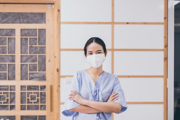 フェイスマスクを着用している患者の女性は、病院でコロナウイルスまたはcovid-19を保護します、コロナウイルス保護マスク