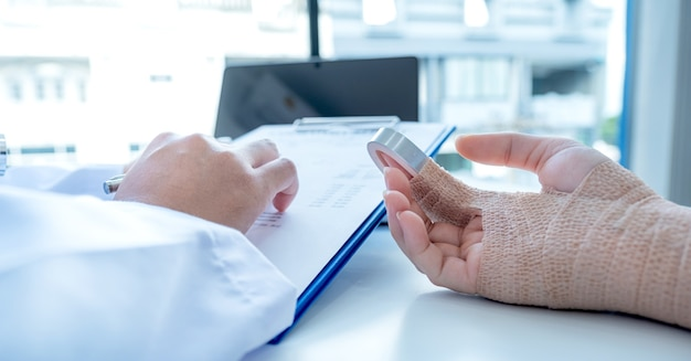 腕の事故の患者、医師は健康診断の結果を報告し、投薬を推奨します。