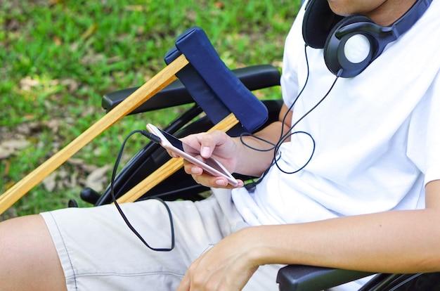 헤드폰을 끼고 옆에 목발을 짚고 휠체어에 앉아 있는 환자 또는 장애인