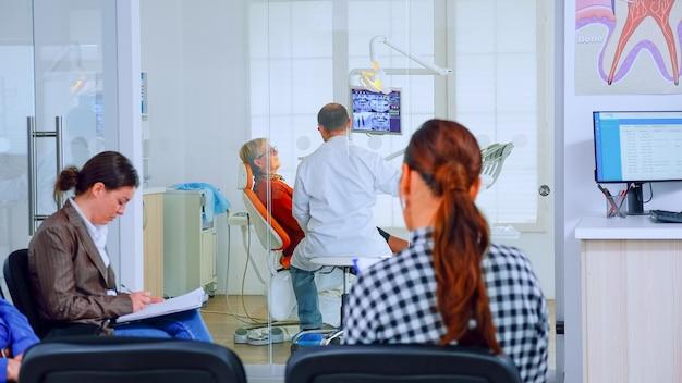医師がバックグラウンドで作業している間、口腔病学クリニックの待合室で椅子に座って口腔病学フォームに記入している患者。混雑したプロの歯科矯正医受付事務所のコンセプト。