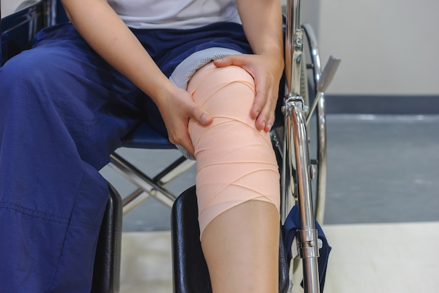 Patients sitting in a wheelchair have pain in the knee that is bandaged.