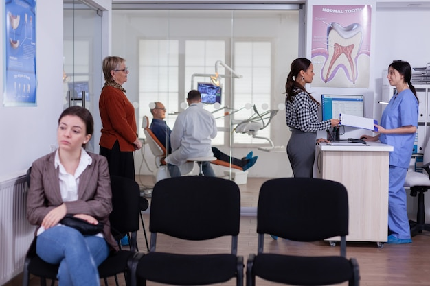 Patients in stomatology reception waiting in line taking filling form, doctor examining senior man discussing teeh healthcare