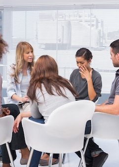 Patients and therapist listening to woman