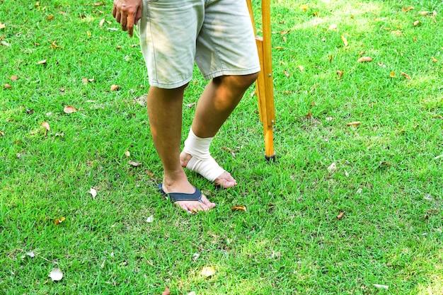 包帯で足首を負傷した患者は、足首を支え、松葉杖を使って芝生を支えます。
