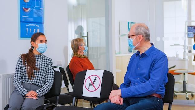 Pazienti con maschera di protezione che parlano seduti su sedie mantenendo la distanza sociale nella clinica stomatologica, in attesa del medico durante il coronavirus. concetto di nuova normale visita dal dentista nell'epidemia di covid19