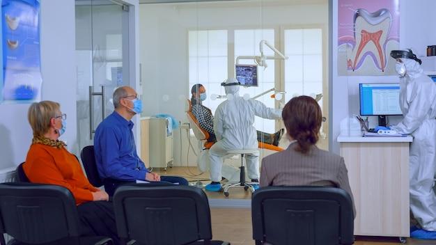 보호 마스크를 쓴 환자들이 치과 진료실에서 의사를 기다리는 동안 구강 전문의가 ppe 정장을 입고 배경에서 일하고 있습니다. 코로나바이러스 발생 시 새로운 일반 치과 방문의 개념.