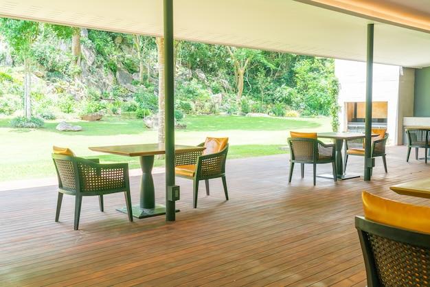 정원 표면이있는 발코니에 파티오 의자와 테이블