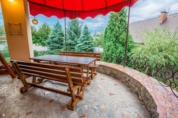 家族の家のパティオ。ベンチが付いている木のテーブル。スイング