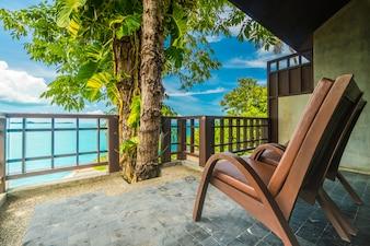 海と海の景色を囲む椅子付きのパティオまたはバルコニー