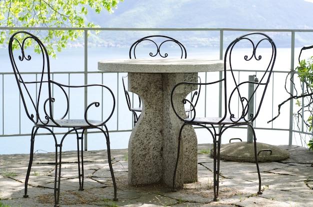 돌 테이블과 호수 너머로 볼 수있는 의자가있는 파티오