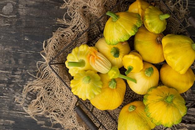 Патиссон, сквош, тыква в форме блюда, сырые овощи на темном деревянном фоне