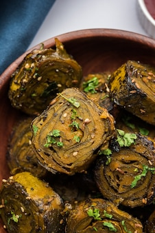Patra or paatra or alu vadi is a popular maharashtrian and gujrati snack recipe made using colocasia leaves, rice flour and flavourings spices, tamarind, and jaggery, selective focus