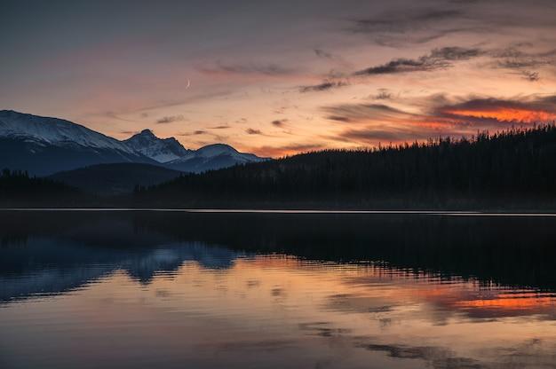 산 범위와 일몰에 달 반사와 패트리샤 호수