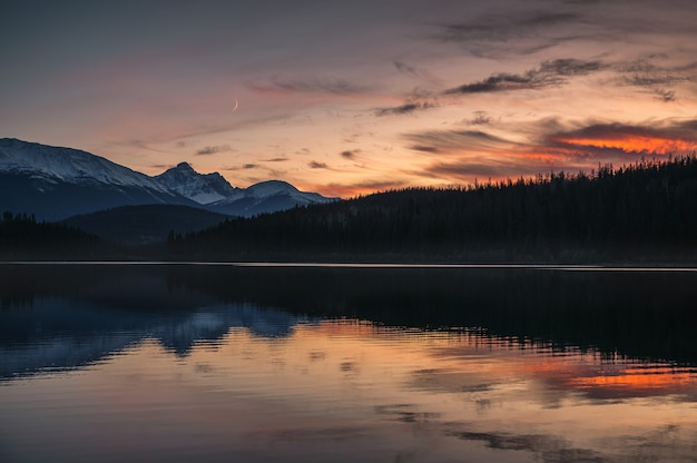 Patricia lake with mountain range and the moon reflection at sunset