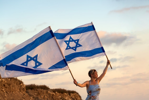 Patriot jewish women in a blue dress holds the flag of the israel in her hands at sunset outdoors