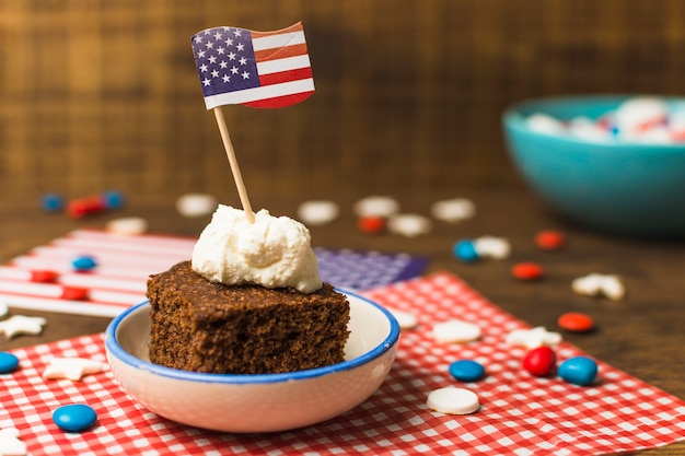 Patriotic 4th of july cake with usa flag and candies on wooden table