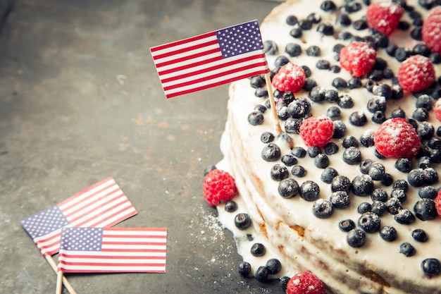Patriotic american flag cake with blueberries and strawberries on vintage white background