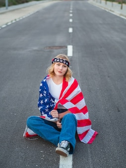 Patriotic caucasian sitting in the middle of the road with the us flag draped around her