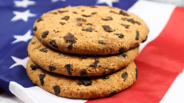 Patriotic cookies. three rounded traditional chocolate chip cookies on the background of the flag of the united states of america. delicious sweet pastries, dessert. america's favorite treat.