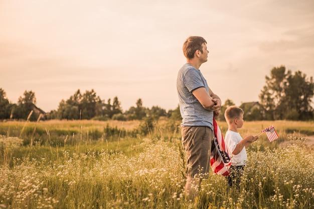 Патриотическая семья держит американский флаг в поле