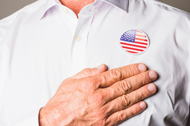 A patriotic man with usa badge on his white shirt touching hand on his chest