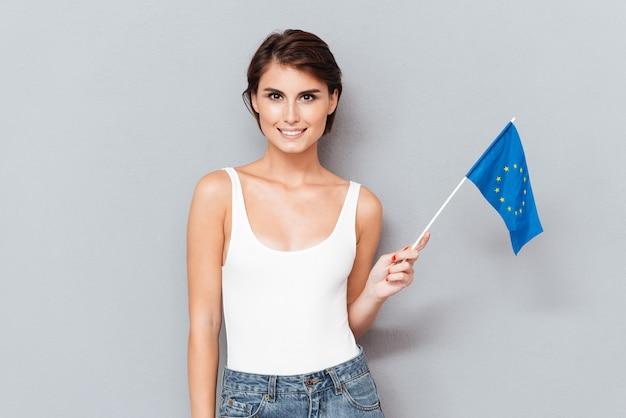 회색 배경 위에 유럽 국기를 들고 애국 웃는 여자