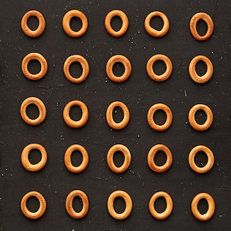 Pattern of bakery products bagels on dark background