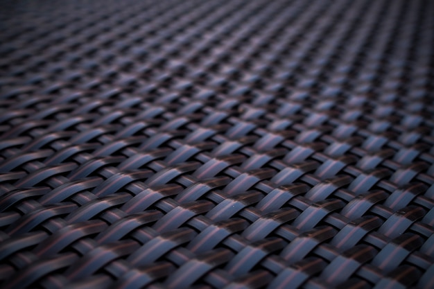 Pattern of black background designed from handicraft weave texture wicker surface for furniture material.