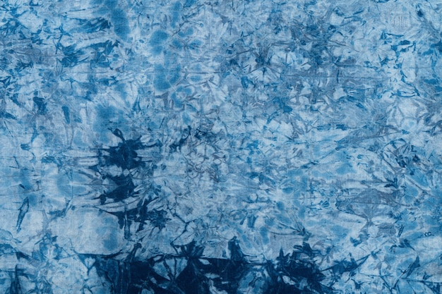 Pattern of blue dye on cotton cloth, dyed indigo fabric background and textured