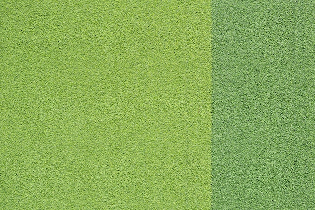 Pattern of bright and dark artificial green grass for texture and background