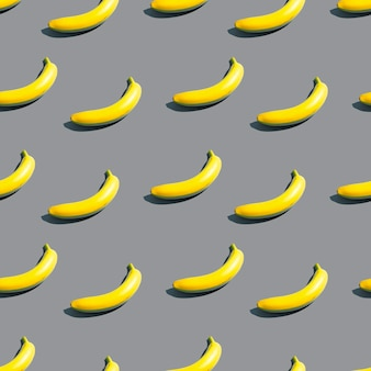 Pattern of bright yellow bananas on a blue background. creative design background in color of the year