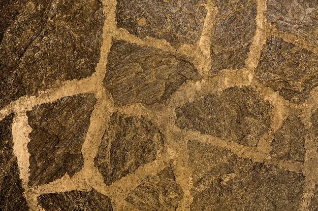 古い石の壁のパターン茶色の不均一なひびの入った本物の石の壁の表面をセメントで