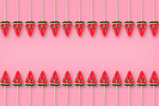 Pattern of candy in shape of watermelon on pink background