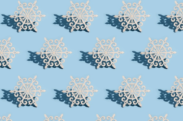 Pattern of christmas tree decoration in the form of snowflakes on a blue background: new year minimalistic concept