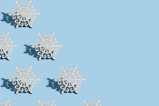Pattern of christmas tree decoration in the form of snowflakes on a blue background with copy space: new year minimalistic concept