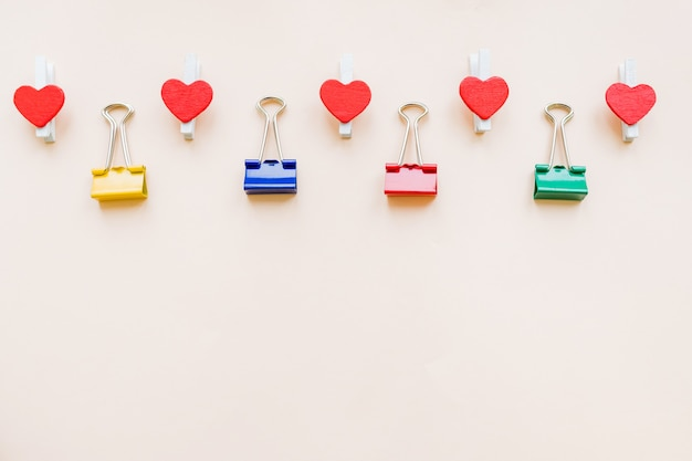 Pattern of colorful binder clips and red hearts on pastel paper background
