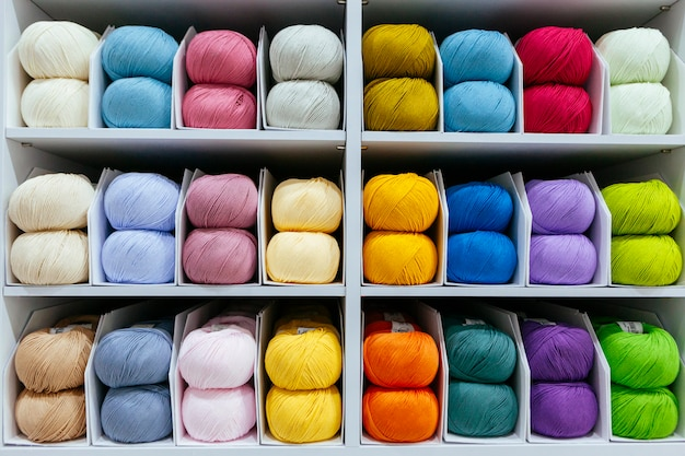 Pattern of colorful different wools yarns organized by color on a retail shop
