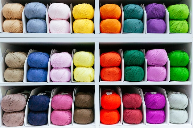 Pattern of colorful different wools yarns organized by color with creativity on a shelf