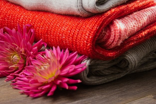 Pattern of colorful knitted sweaters closeup. handmade merino wool product. a stack of folded clothes with flowers.