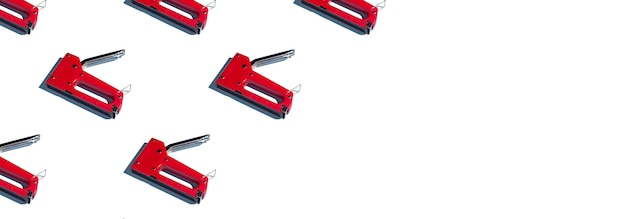 A pattern of construction staplers, copyspace on a white background. construction tools, repairs. background for the design.