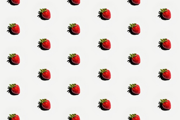 Pattern of delicious strawberries on white surface