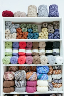 Pattern of different kind of wool yarns organized by color on a retail shop
