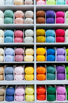 Pattern of different wool yarns organized by color on a white shelf