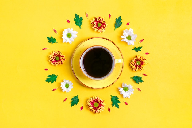Pattern of flowers of red and white asters, green leaves and cup of hot coffee americano on yellow background flat lay