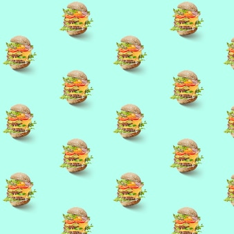 Pattern of flying hamburger with vegetables and cheese on a green