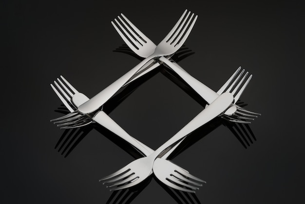 Pattern in the form of a diamond with many silver forks on a black mirror background. concept, texture.